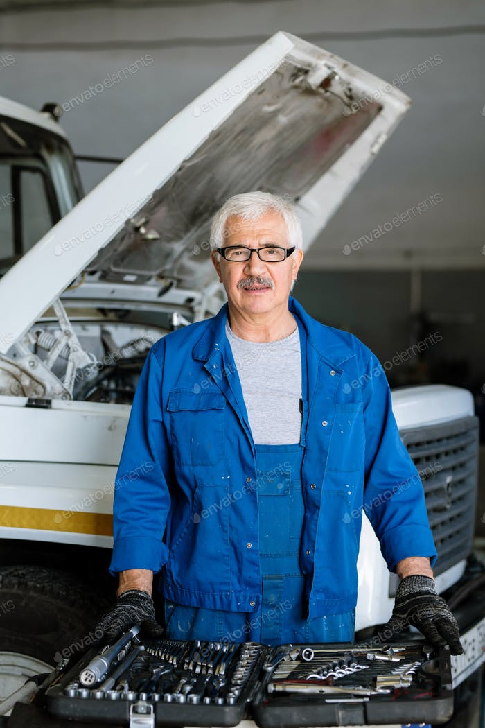 Mature technician choosing worktools while serving one of machines