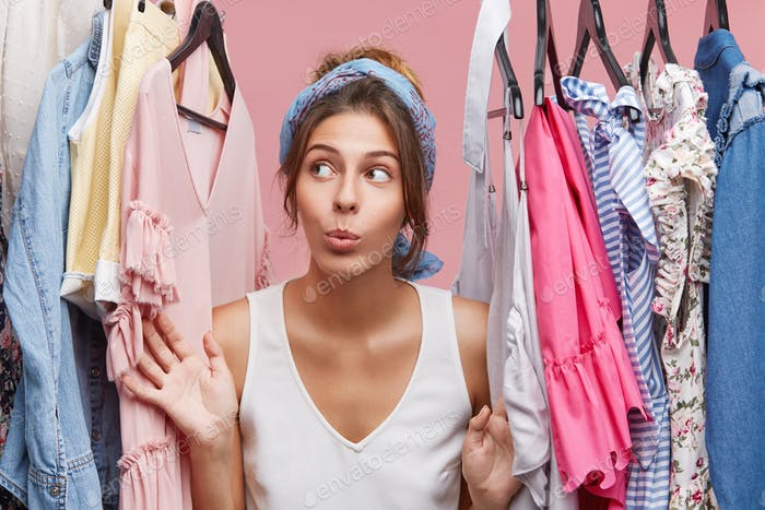 Attractive woman dressed casually, looking with doubts aside while standing near hangers with clothe