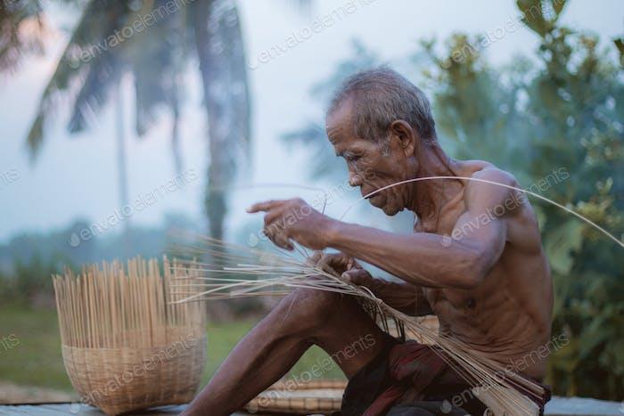 Viejo Hombre están tejiendo cesta de Tailandia