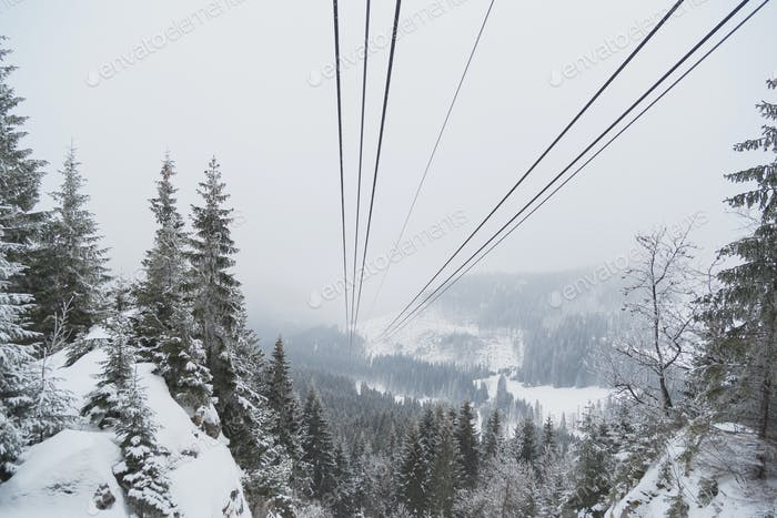 Cableway in the mountains in winter. Perspective view of the mountain woods and rope ropeway