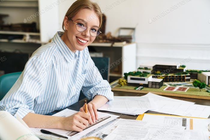 Photo of woman architect working with drawings while designing draft