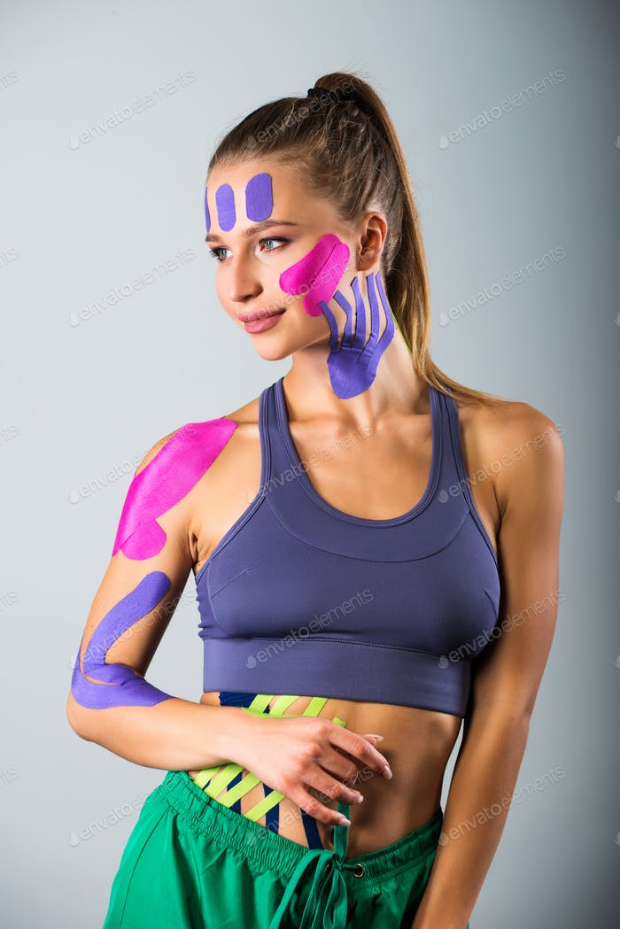 Portrait of sports woman in kinesio therapeutic tapes