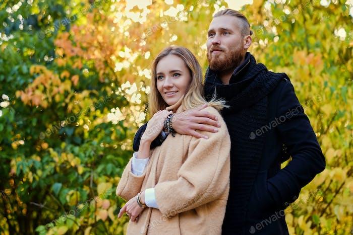 Redhead male hugs cute blonde female in autumn wild nature backg