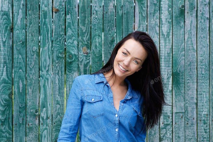 Улыбающаяся брюнетка женщина с голубой рубашкой
