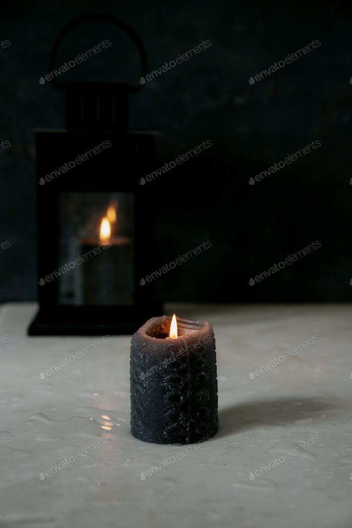 Teilweise verbrannte schwarze Kerze und Vintage Laterne mit brennender Kerze