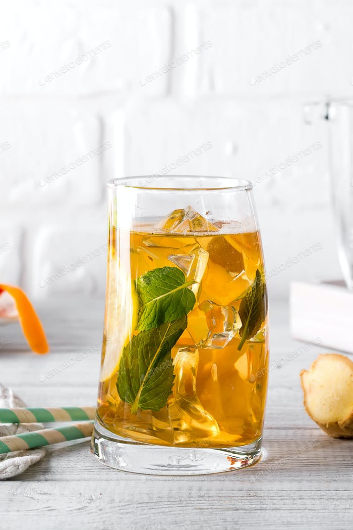 Traditional iced tea with lemon, ginger and ice in tall glasses on white background