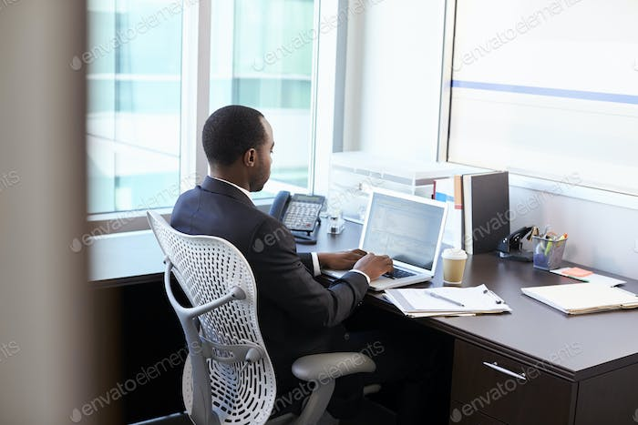 Doctor Working On Laptop At Desk In Office