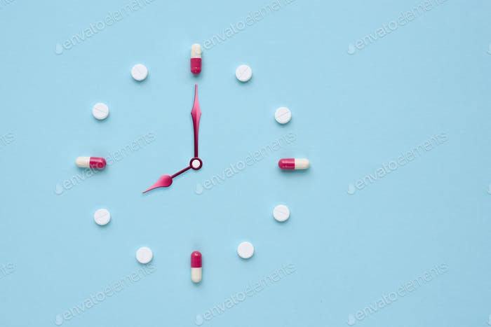 Clock created from pills and capsules on pastel blue background