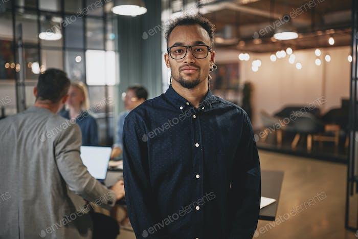 Уверенный молодой бизнесмен, стоящий в современном офисе