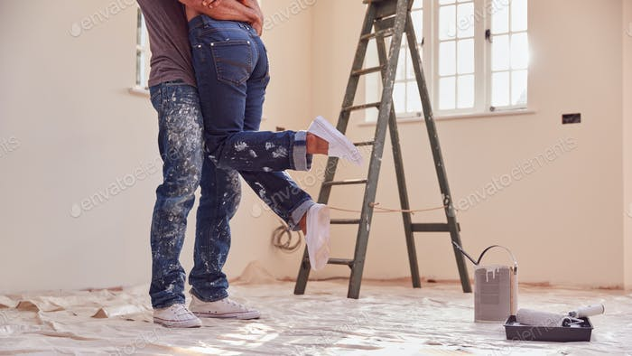 Close Up Of Couple Hugging As They Decorate Room In New Home Together