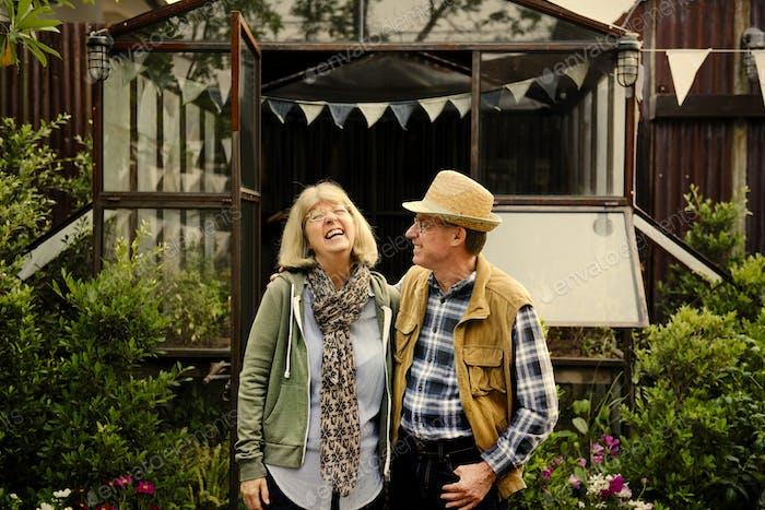 Senior couple planting vegetables at garden backyard