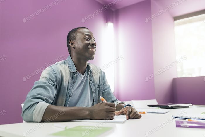 Handsome african man learning at classroom.