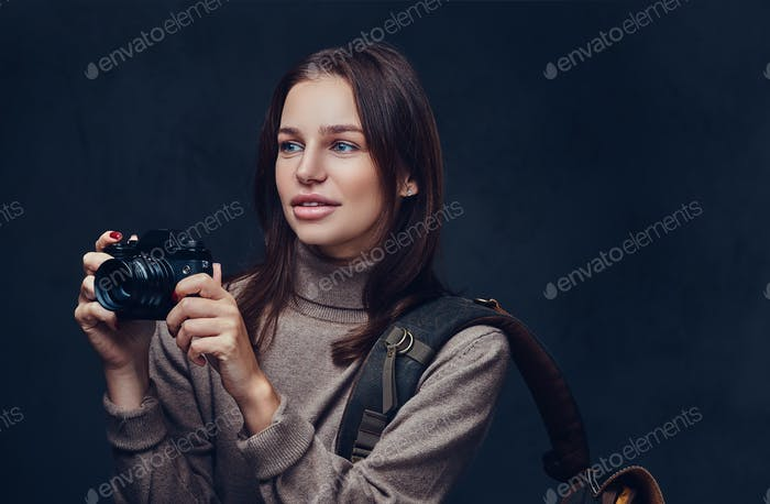 A woman with backpack holds compact photo camera.