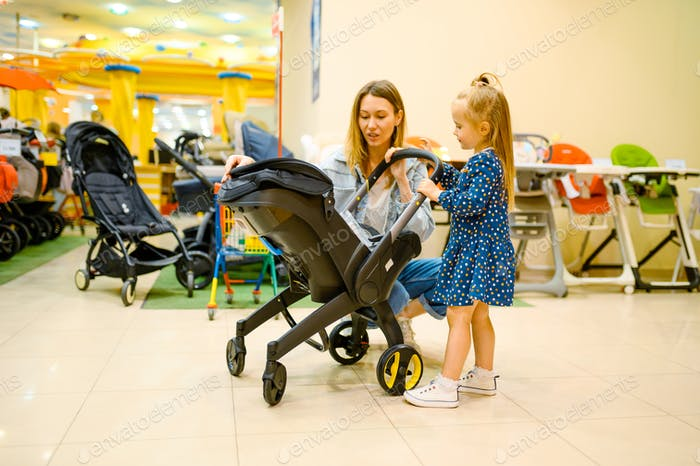 Mother and little daughter choosing baby stroller