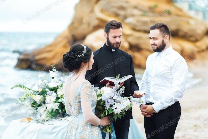 свадебная пара на берегу океана со священником