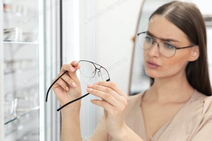 Portrait of beautiful young woman choosing spectacles