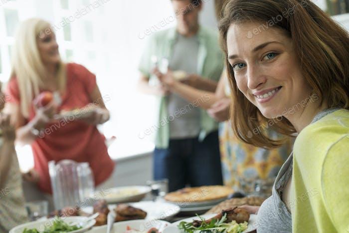 Ein Familientreffen für eine Mahlzeit. Erwachsene und Kinder an einem Tisch.