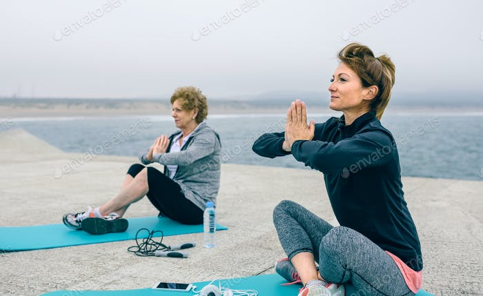 Young and senior woman exercising sitting outdoors