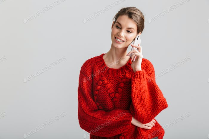 Image of young cheerful woman smiling and talking on cellphone