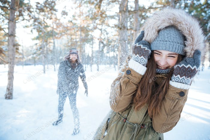 Happy young couple playing snowballs outdoors