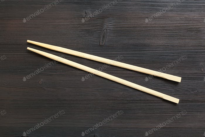 wooden disposable chopsticks on dark brown table