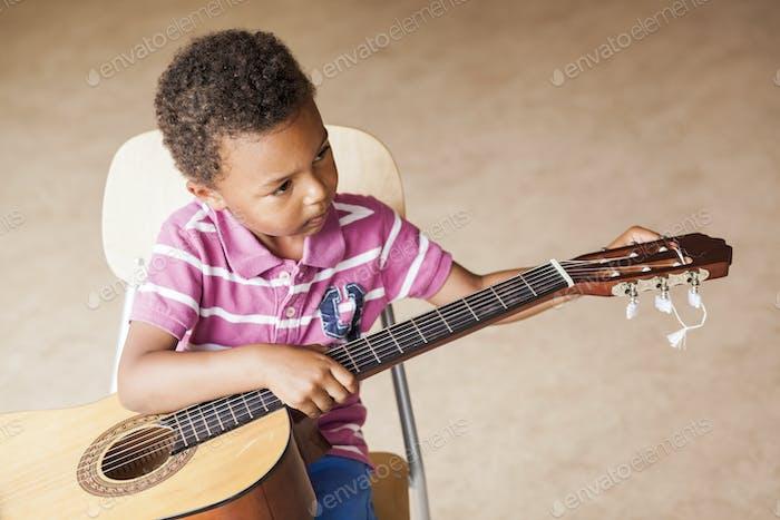 Erhöhte Ansicht des Jungen, der Gitarre spielt, während er auf dem Stuhl sitzt