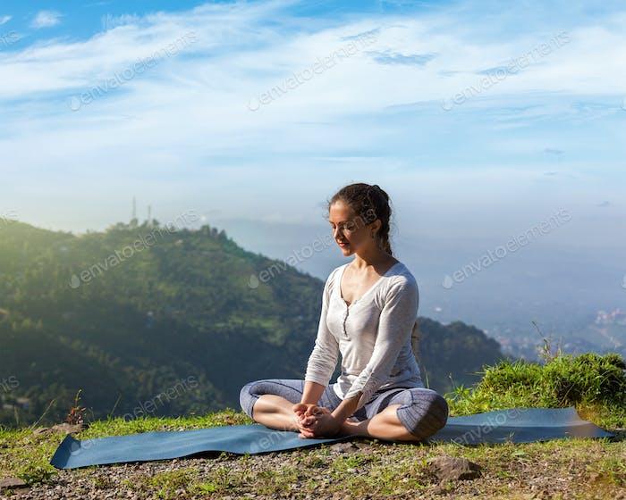 Woman practice yoga asana Baddha Konasana outdoors