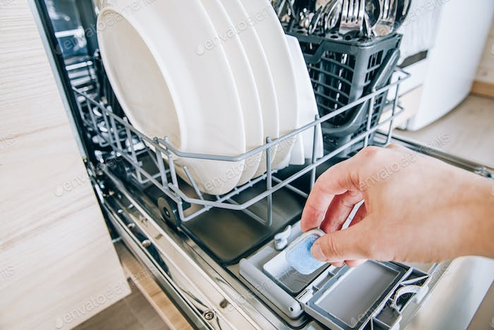 Woman hand putting tablet in dishwasher detergent box. Dishwasher machine full loaded.