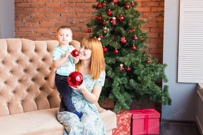 Mama mit Kind spielen am Weihnachtsabend, Winterwochenenden, gemütliche Szene