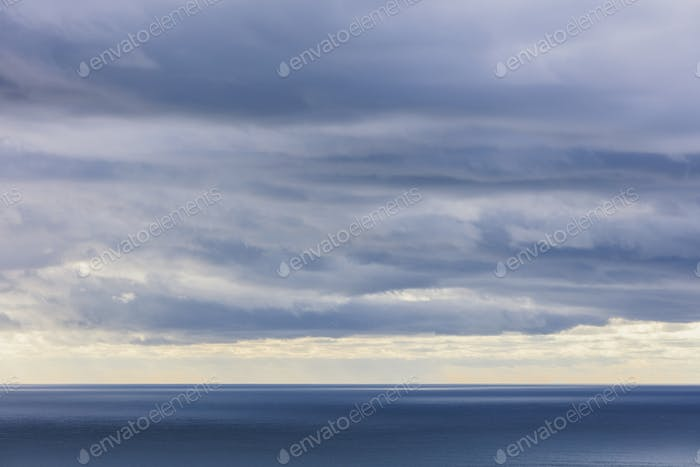 Storm clouds clearing over expansive ocean, dappled sunlight on water, northern Oregon coast
