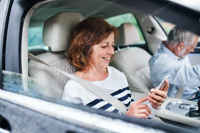 Happy senior couple with smartphone sitting in car, going on trip