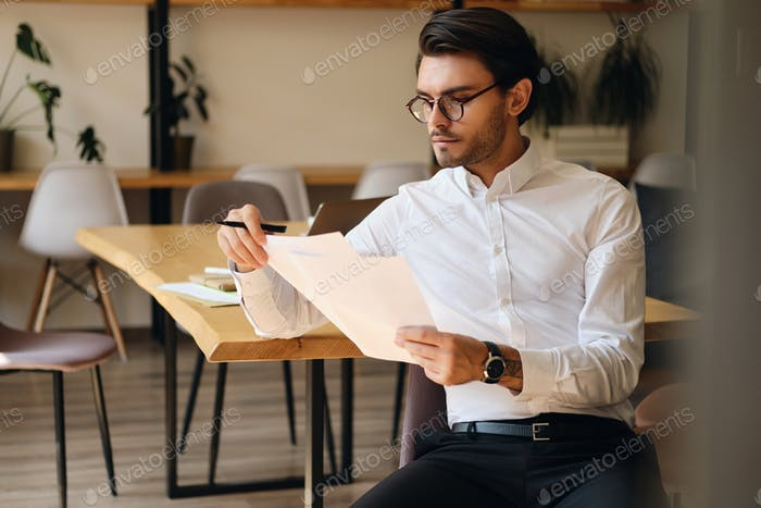 Young serious businessman in eyeglasses thoughtfully working with papers in modern office