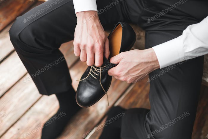 Man wearing brown leather classic shoes, black trousers and white shirt, business style