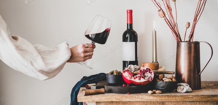 Womans hand holding glass of wine and snacks, wide composition