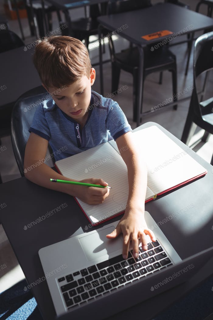 Boy using laptop while writing in book at school