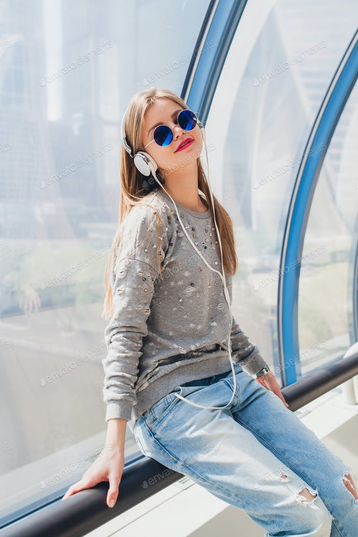 young hipster woman in casual outfit having fun listening to music