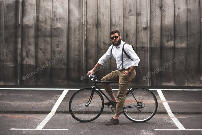 serious fashionable bearded man in sunglasses sitting on bicycle
