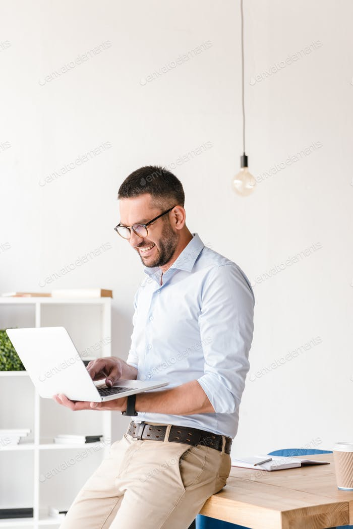 Handsome joyful man wearing white shirt sitting on table in offi
