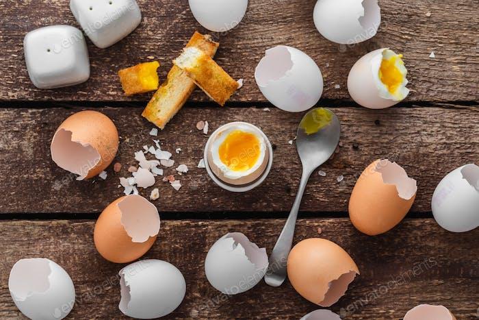 Gesundes Frühstück mit weichem gekochtem Ei und leeren Muscheln im rustikalen Stil