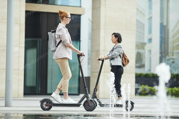 People Riding Electric Scooters in City