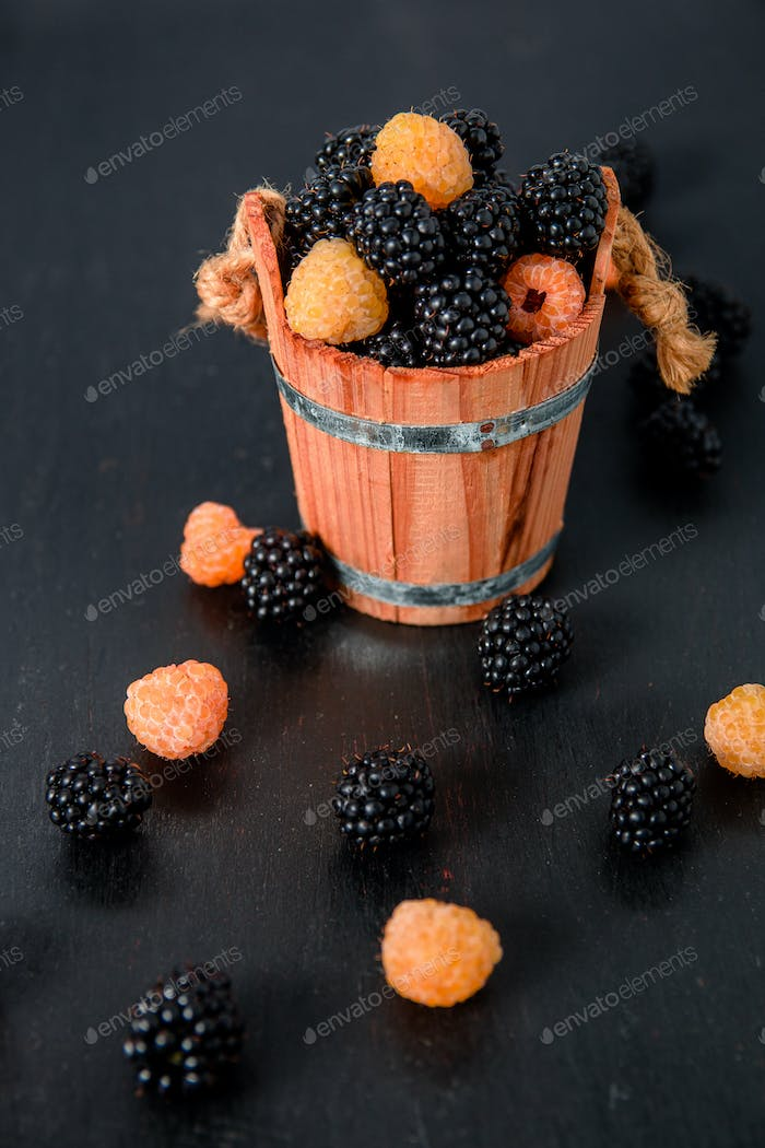 Black and yellow raspberries in a wooden basket  on   table. Close up.