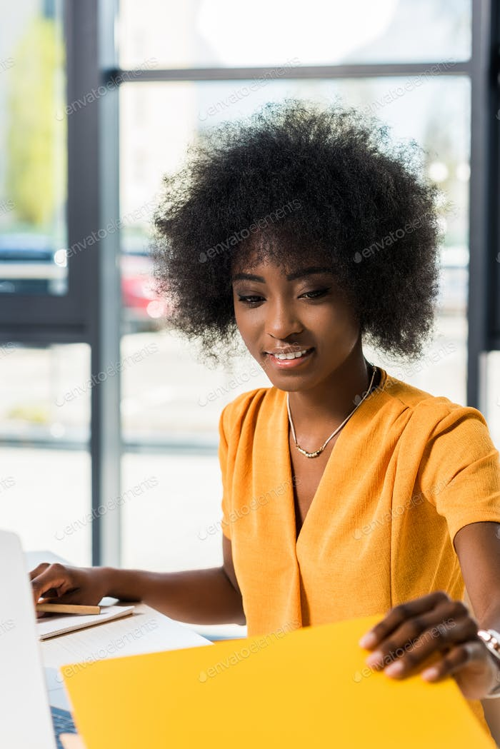 smiling african american freelancer en el lugar de trabajo en casa