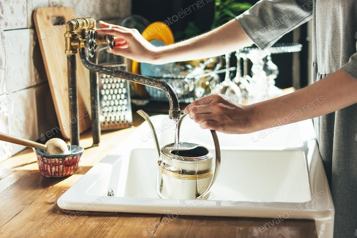 Young woman in grey dress pours water into kettle in kitchen