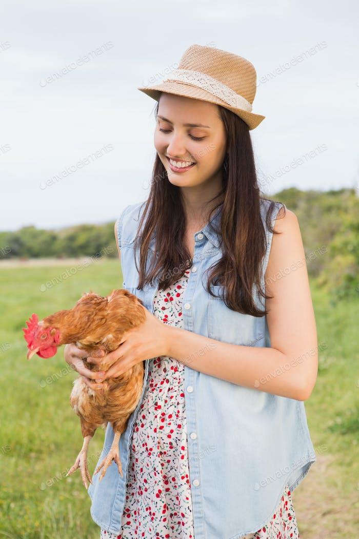 glücklich Brünette halten Ihr Huhn auf ein sonnigen Tag