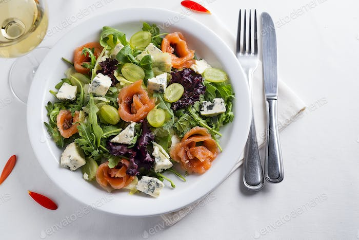 Delicious salad with salmon, grapes and cheese on a white background