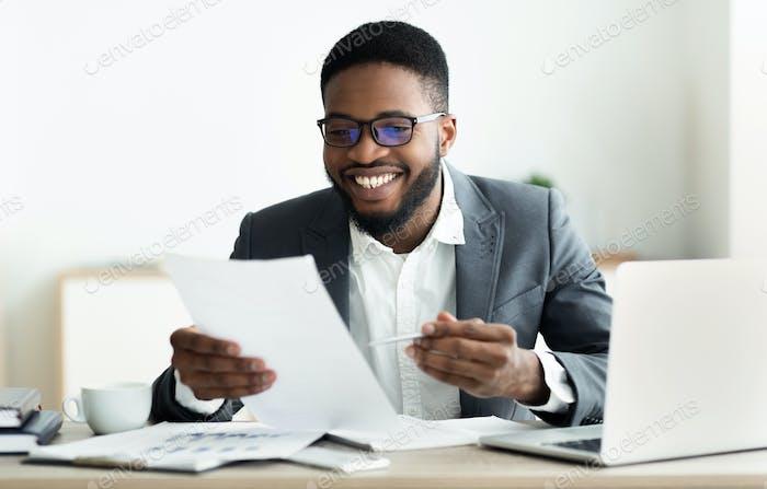 Lächelnd schwarz Geschäftsmann Überprüfung Berichte in modernen Büro