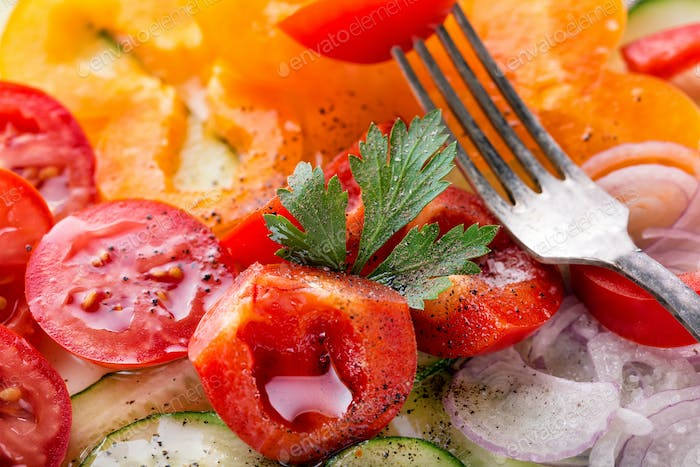 Fragment of fresh vegetable salad with a fork
