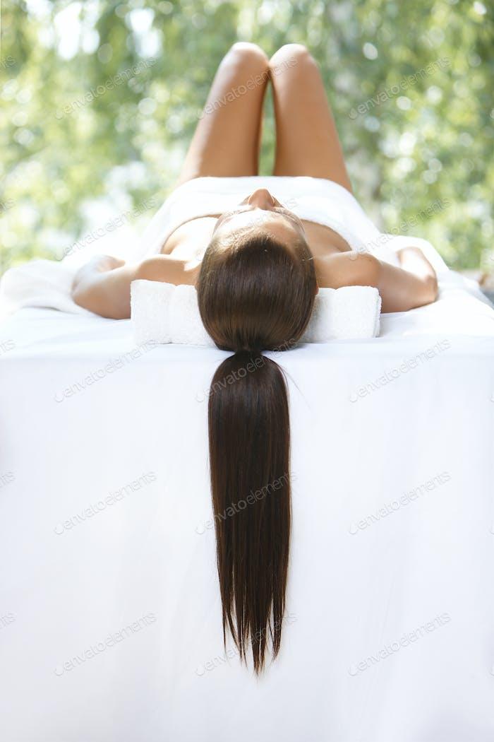 Schöne Frau ruht auf Spa-Bett