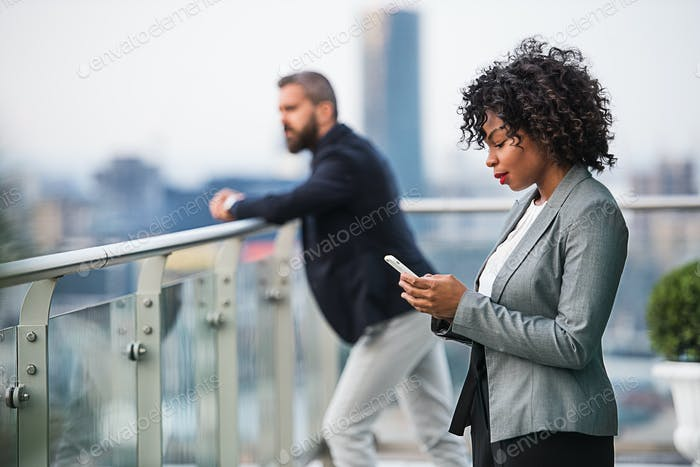A portrait of a businesswoman with smartphone standing on a terrace.