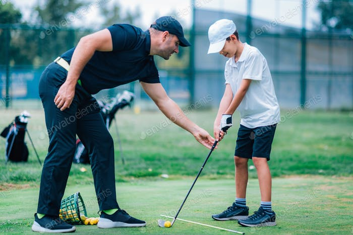 Personal golf lesson. Golf instructor with young boy on a golf driving range.